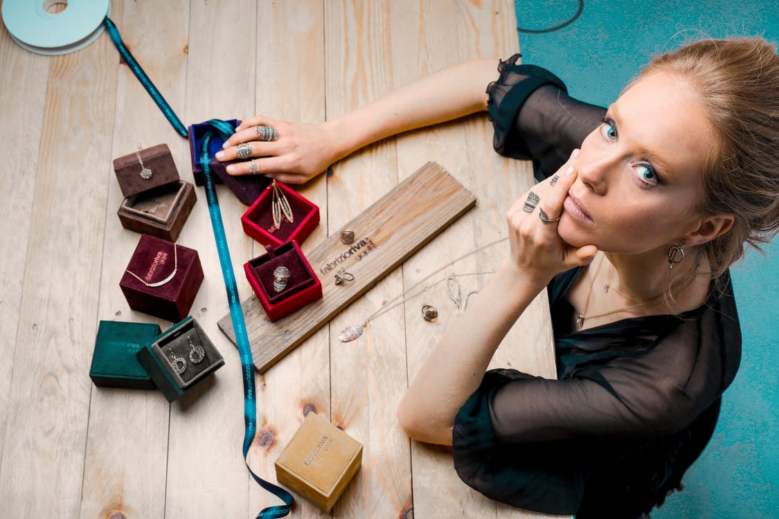 From above serious businesswoman looking up at camera while sitting at wooden table with small jewelry boxes with bijouterie and decorating with ribbon as present