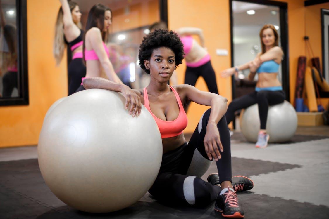 Junge Ethnische Frau Mit Passendem Ball, Der Auf Boden Während Des Trainings In Der Modernen Turnhalle Sitzt