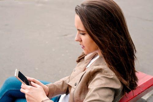 Foto stok gratis alat, berambut cokelat, duduk, handphone
