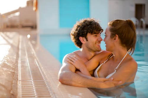 Man and Woman Embracing While on Swimming Pool