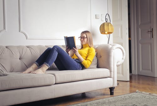 Woman in Yellow Long Sleeve Shirt and Blue Denim Jeans Sitting on White Couch