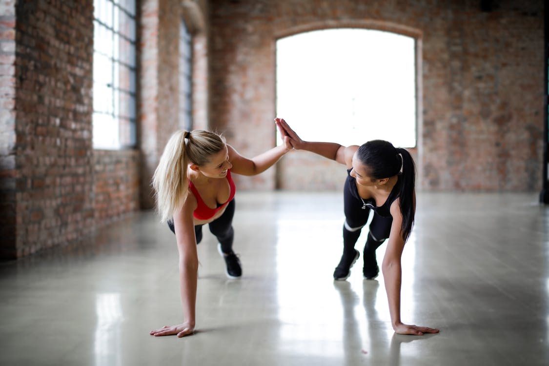 Fit smiling women in sportswear looking at each other and giving high five while doing push up exercise on gray glossy floor against blurred interior of spacious workout room with brick walls and big windows