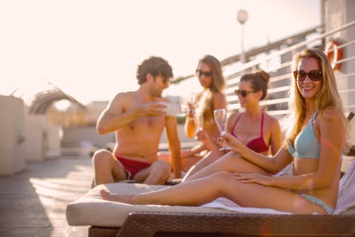 Happy friends drinking tasty beverage while sunbathing together on beach in sunny summer day