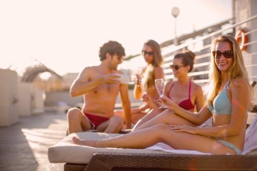 晴れた夏の日にビーチで一緒に日光浴しながらおいしい飲み物を飲む幸せな友達