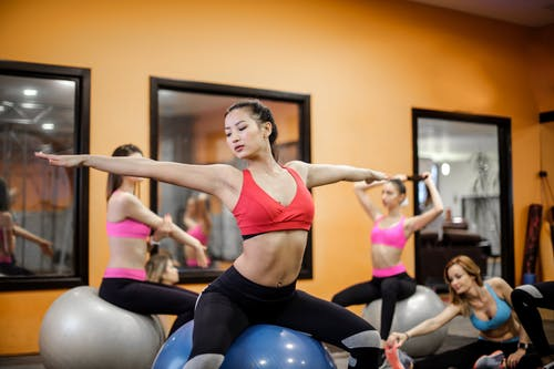 Serious slim ethnic female athlete in sportswear sitting on fit ball with arms outstretched and stretching body while training with other ladies in contemporary fitness center