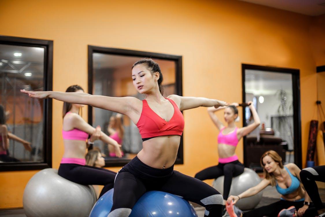 Молодые гибкие многорасовые женщины практикуют пилатес на спортивном мяче в современной студии