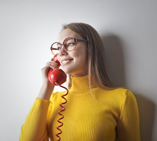 Woman in Yellow Sweater Holding Red Telephone