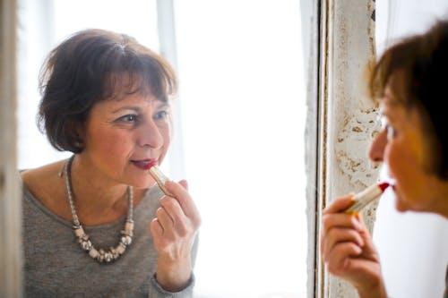 Photo D'une Femme Plus âgée Appliquant Du Rouge à Lèvres Devant Le Miroir