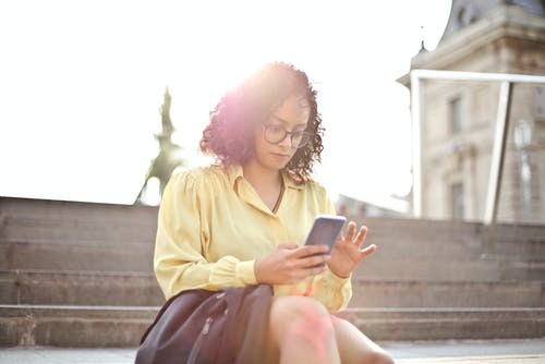 Selective Focus Photo of Woman in Yellow Dress Shirt Sitting on Stairs Using Her Phone