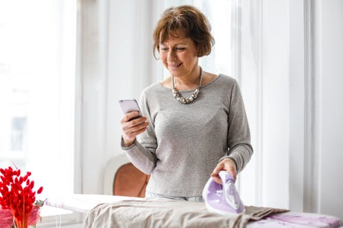 Joyful housewife using smartphone with pleasure while ironing clothes at home