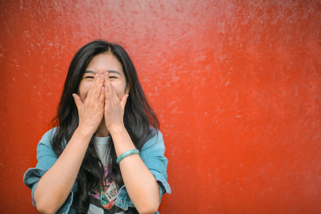 веселая этническая женщина против ярко красной окрашенной стены