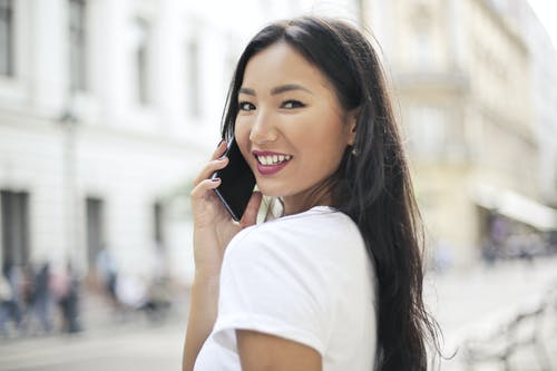 Selective Focus Photo of Smiling Woman in White T-shirt Talking on the Phone