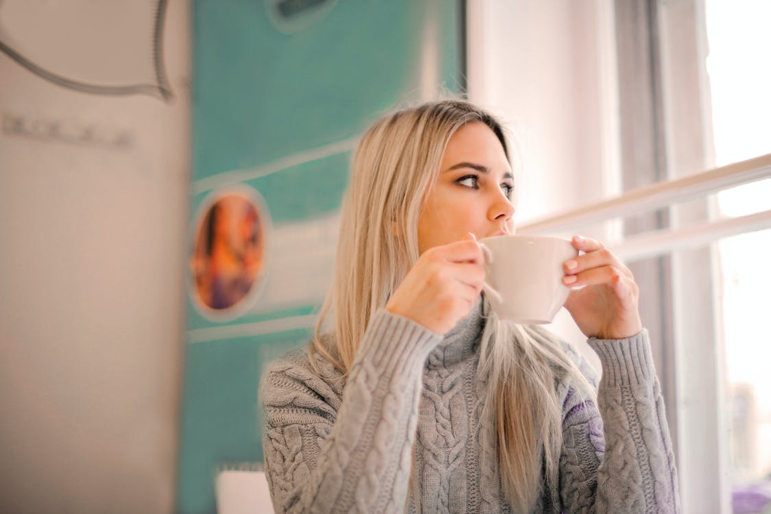 Selective Focus Photo of Woman in Gray Sweater Drinking from White Ceramic Mug While looking Away