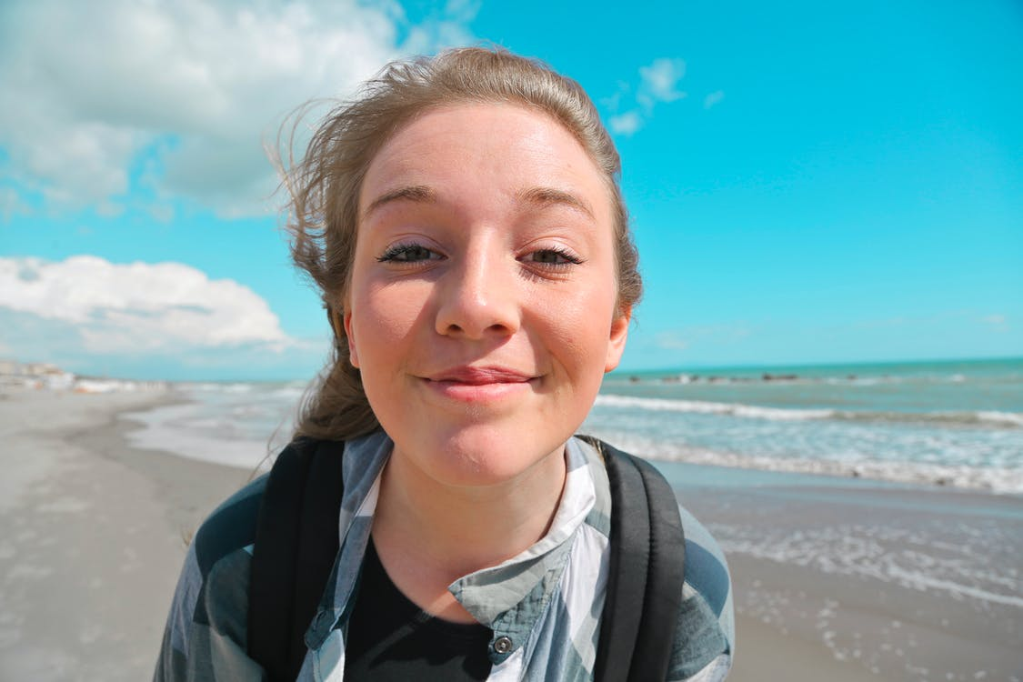 Portrait Photo of Smiling Woman in Standing at the Beach on a Sunny Day