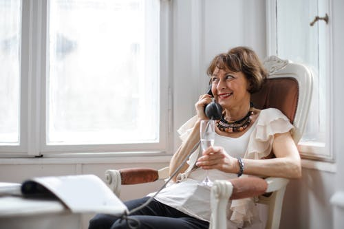 Happy middle aged woman making phone call and drinking tasty at home