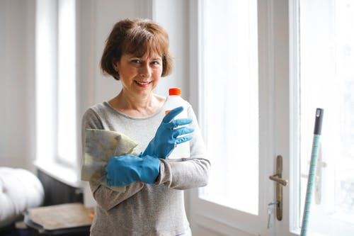 Joyful woman in casual clothes standing near window with rag and cleaning agent and smiling at camera while engaged in household in light modern apartment