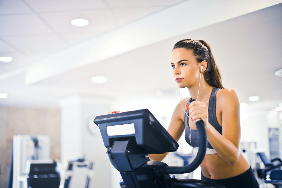 Serious fit woman in earphones and activewear listening to music and running on treadmill in light contemporary sports center