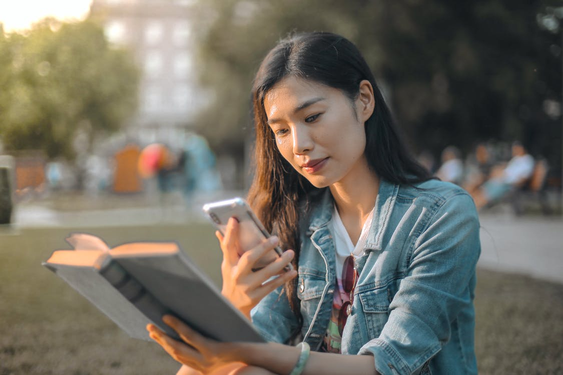Selective Focus Photo of Woman in Blue Denim Jacket Using Her Phone While Holding a Book