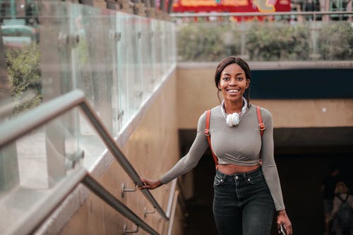 Photo of Smiling Woman in Gray Top and Black Denim Jeans Walking Up Some Stairs