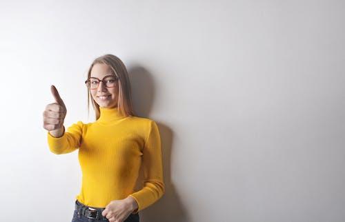 Foto Di Donna In Maglione Dolcevita Giallo, Jeans Blu Denim E Occhiali Che Danno Il Pollice In Alto