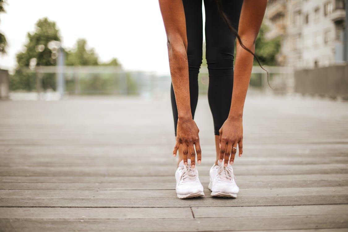 From below crop slender female athlete in sportswear and white sneakers doing standing forward bend exercise for stretching body on wooden floor of street sports ground against blurred urban environment in daytime