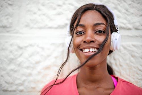 Photo Mise Au Point Sélective De Femme Souriante En Chemise Rose Portant Des écouteurs Blancs Debout Devant Un Mur Blanc
