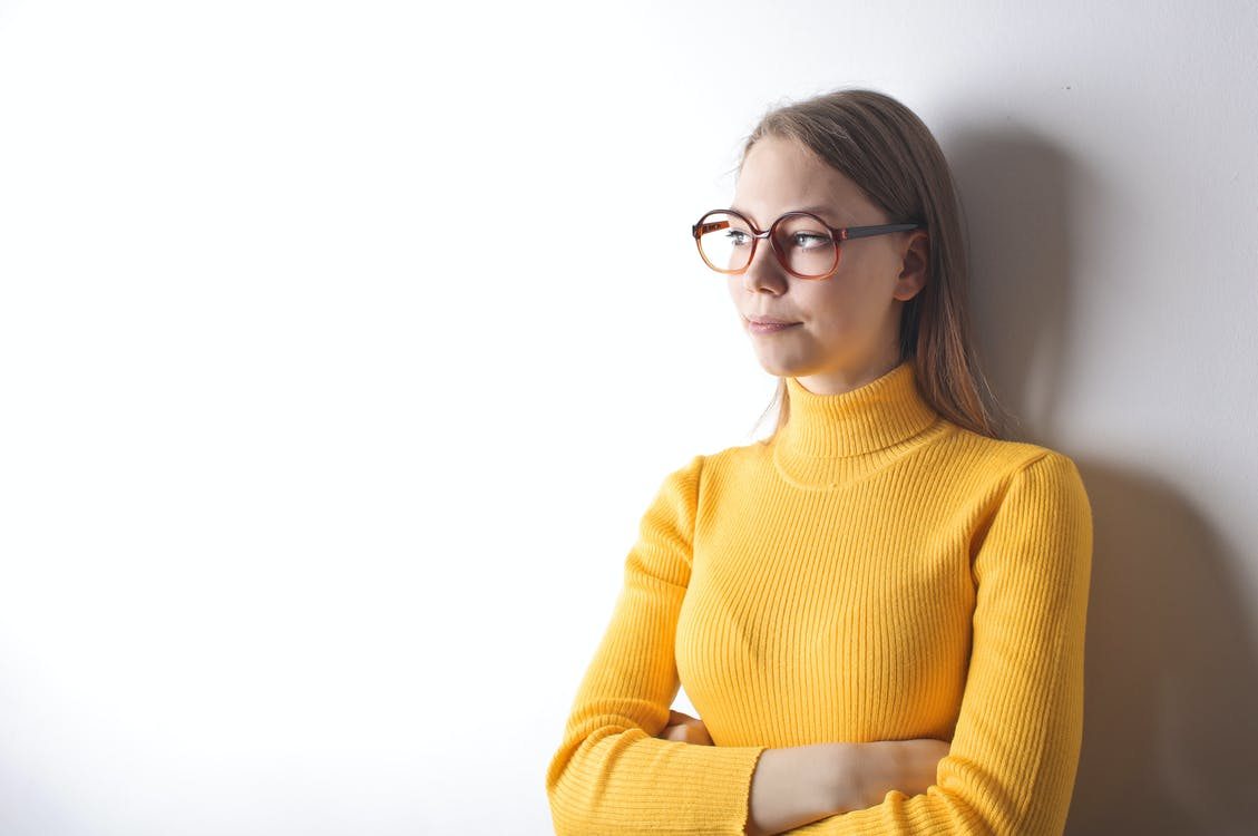 Portrait Photo of Woman in Yellow Turtleneck Sweater and Black Framed Eyeglasses Standing In Front of White Wall While Looking Away