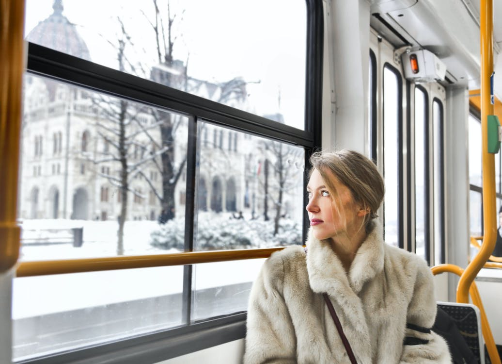 Cam young woman in warm clothes in public transport