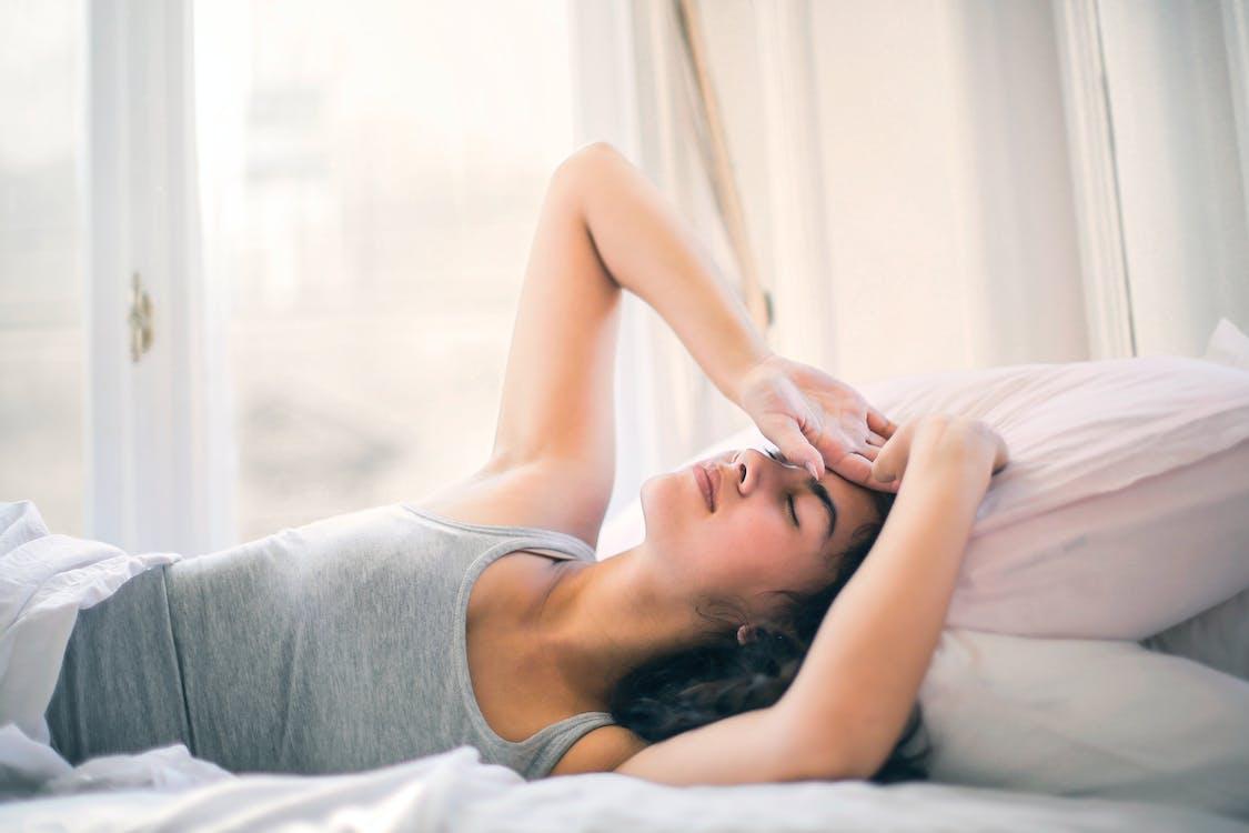Vrouw In Grijze Tanktop Slapen Op Wit Bed