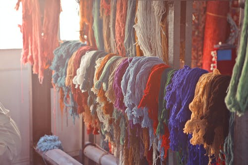 Skeins of multicolored threads for needlework hanging on wooden rack in light workroom