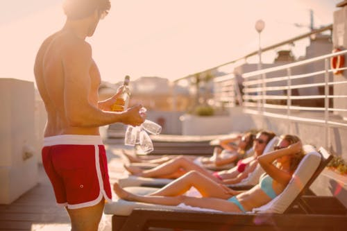 Young man offering drinks to sunbathing girlfriends