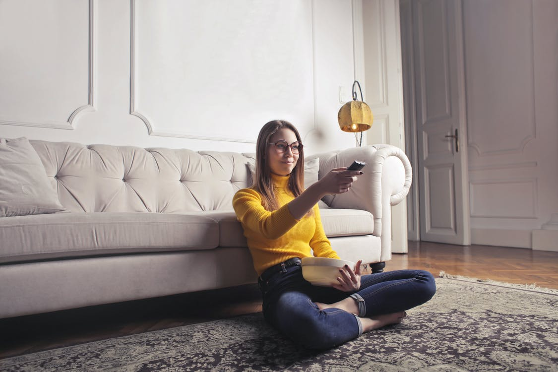 Young woman relaxing at home and watching movie