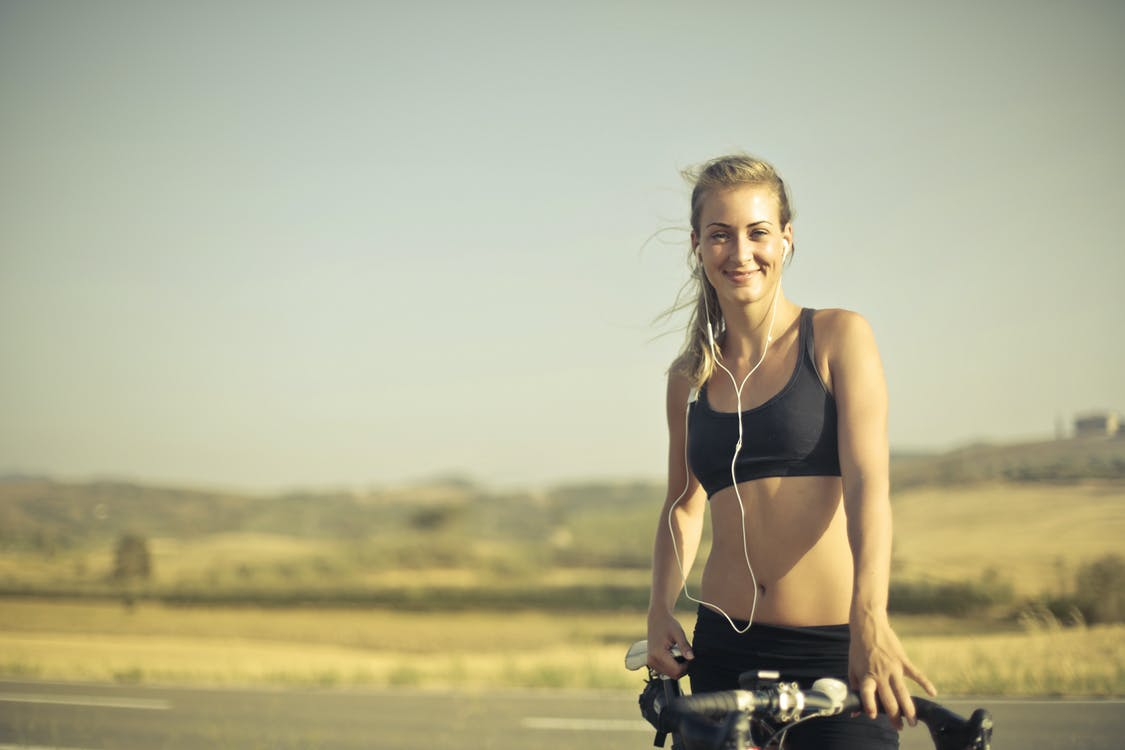Selective Focus Photo of Smiling Woman in Black Active Wear with Earphones on  Standing Next to Her Bicycle by the side of the Road