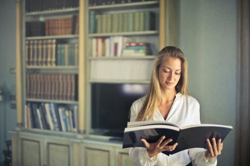 Photo of Standing Woman in White Long Sleeve Shirt Reading a Book