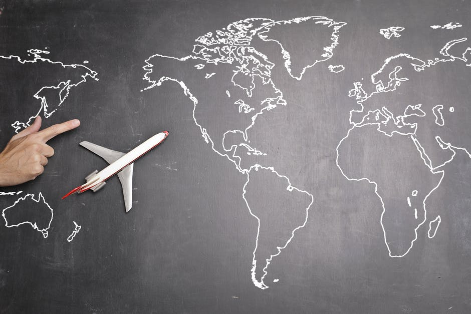 Airplane over world map on blackboard