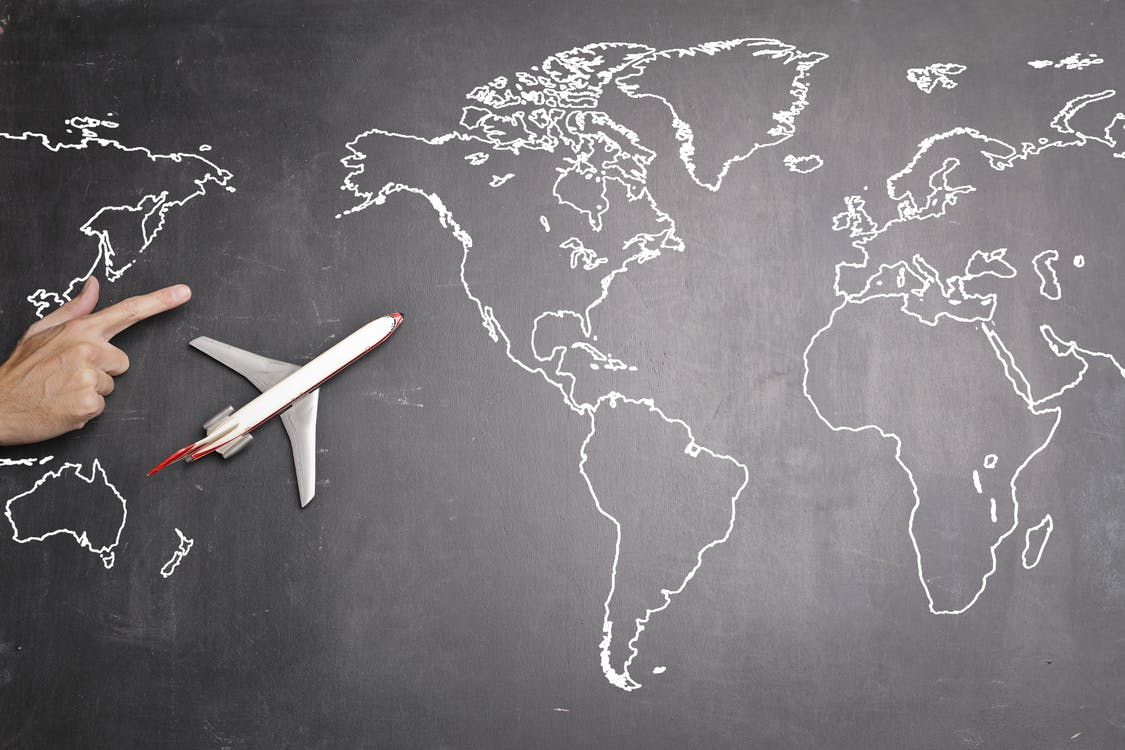 Top view of miniature airplane placed on over gray world map with crop hand of anonymous person indicating direction representing travel concept