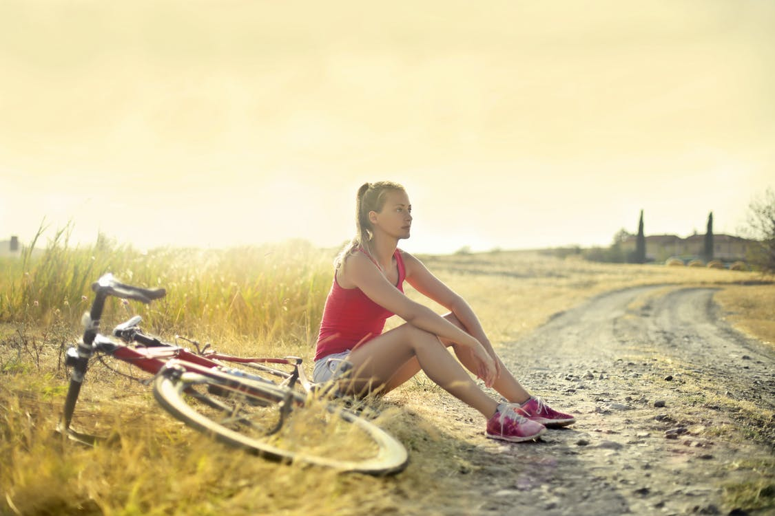Photo of Woman in Red Tank Top Sitting by the Side of a Dirt Road Next to a Her Bike