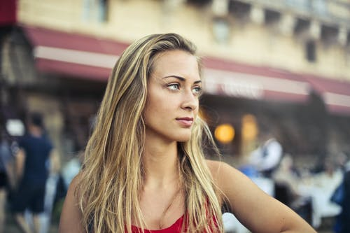 Selective Focus Portrait Photo of Woman in Red Tank Top Looking Away