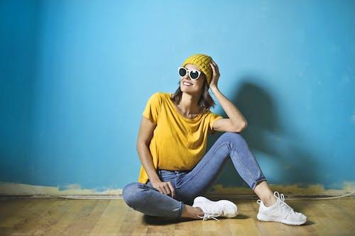 Foto Der Lächelnden Frau Im Gelben T Shirt Und Im Beanie Hut, In Den Blauen Jeans Und In Der Weißen Sonnenbrille, Die Auf Dem Boden Vor Einer Blauen Wand Sitzen