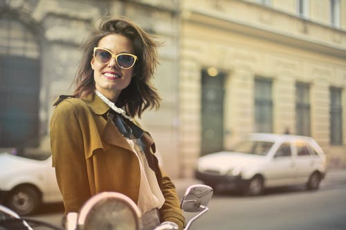 Selective Focus Photo of Smiling Woman in Brown Coat and Yellow Sunglasses Standing on Sidewalk