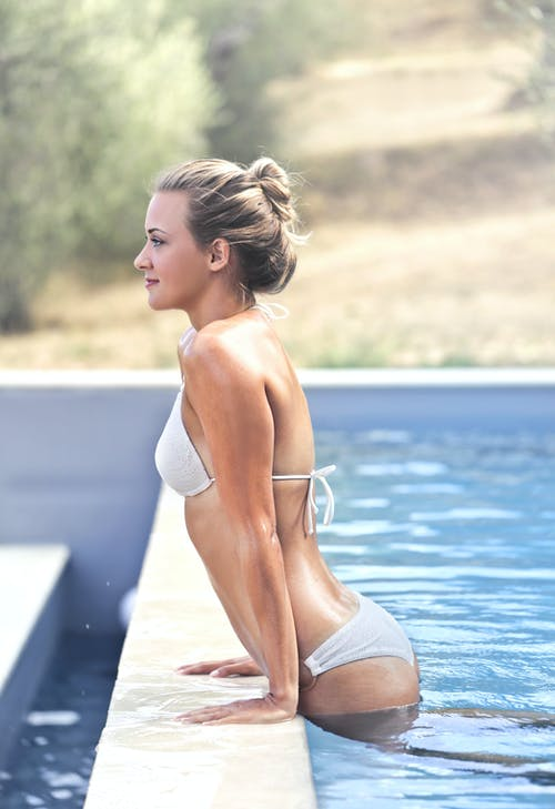 Side View Photo of Woman in White Bikini Getting Out of a Swimming Pool