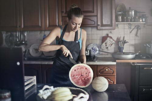 Photo of Woman in Black Apron Slicing a Watermelon In the Kitchen