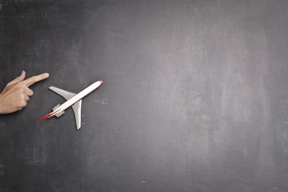 Toy plane and human hand on chalkboard