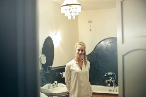 Photo of Smiling Woman in A White Silk Top Standing in a Bathroom