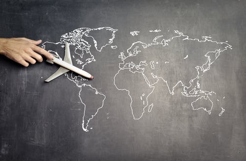 From above of crop anonymous person driving toy airplane on empty world map drawn on blackboard representing travel concept