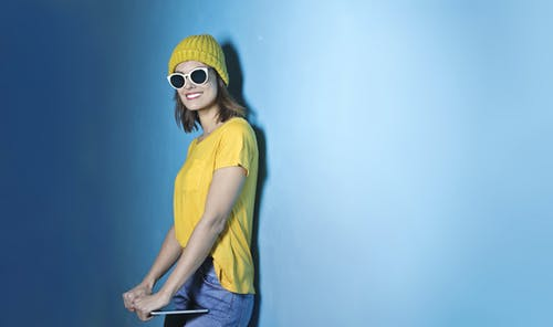 Photo of Smiling Woman in Yellow T-shirt and Beanie, Blue Jeans, and White Sunglasses Standing In Front of Blue Wall While Carrying a Tablet