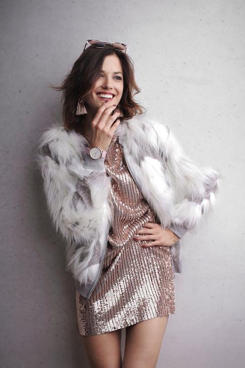 Foto De Mujer Riendo Con Abrigo De Piel Blanco Y Vestido Brillante De Pie Frente A Una Pared Gris