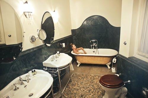Woman Relaxing in a Bathtub Inside a Bathroom