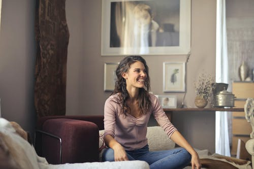 Photo of Laughing Woman in Pink Long Sleeve Shirt and Blue Denim Jeans Sitting on Red Sofa Chair