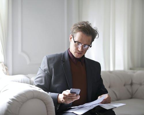 Foto Des Mannes Im Anzug Und In Den Schwarzen Gerahmten Brillen, Die Auf Weißem Sofa Sitzen, Während Sie Ein Telefon Benutzen